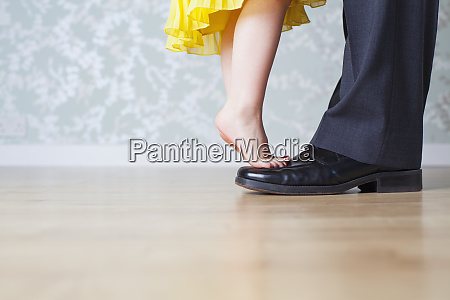 girl on fathers shoes