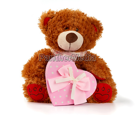 brown curly teddy bear sits and