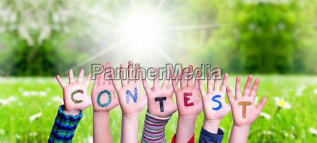 children hands building word contest grass