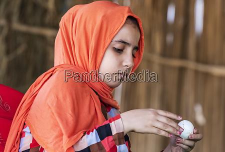 sudanese girl peeling a boiled egg