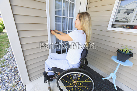 woman in wheelchair locking the front