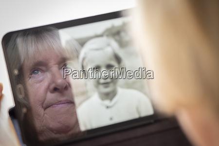 senior caucasian woman looking at old