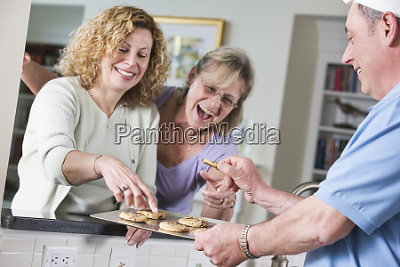 chef serving cookies to mature women