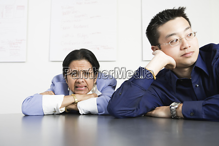 disappointed businesspeople sitting by desk