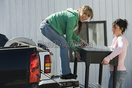 women loading furniture