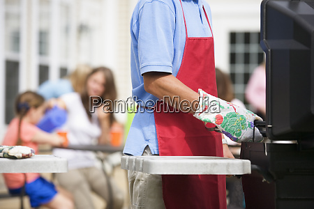 man cooking at family barbeque
