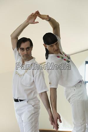 two mid adult men dancing flamenco