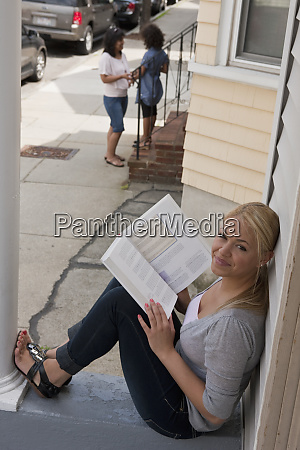 a young woman reading from a