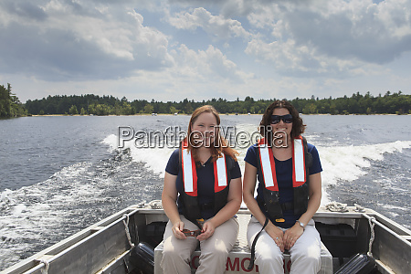 two women in lifejackets sitting in