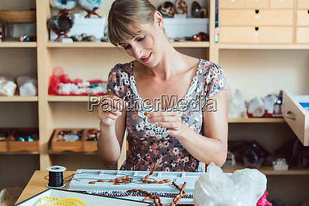 woman making a necklace from gemstones