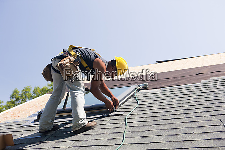 roofer fitting shingle to skylight