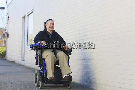 man in electric wheelchair going down