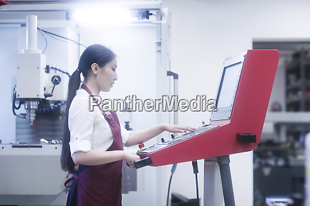 asian woman working on machinery in