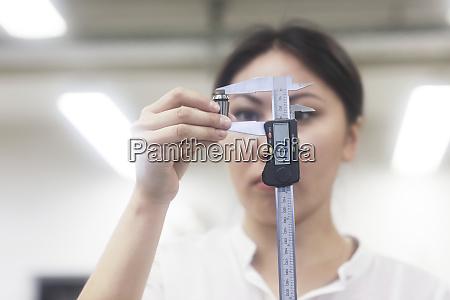 asian woman measuring piece of gadget