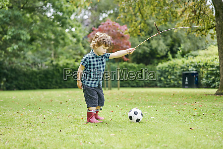 toddler playing with stick and football