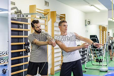 man coaching friend in gym
