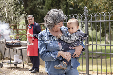 grandmother carrying baby boy at family