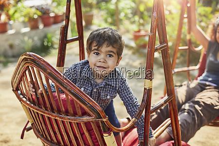 little boy climbing up onto rattan
