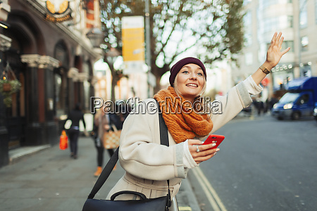 woman with smart phone hailing taxi