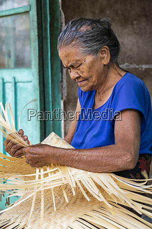 an elderly woman weaving a basket