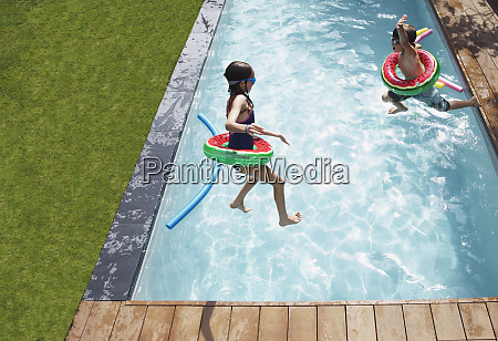 boy and girl jumping into sunny
