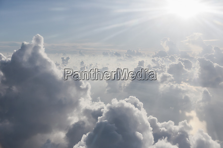 aerial view sunbeams over fluffy clouds