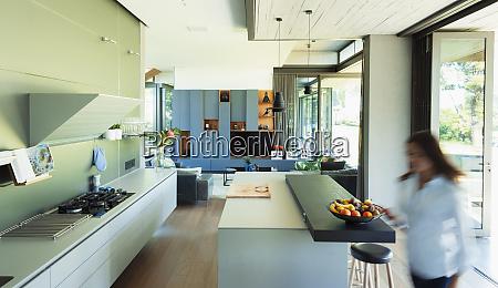 woman walking in modern luxury kitchen