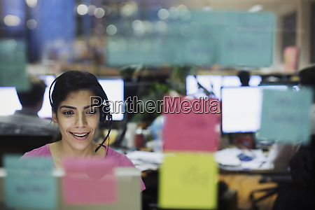 businesswoman with headset working at computer