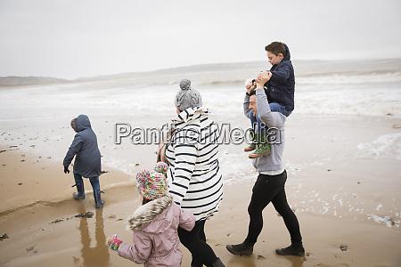 family walking on winter ocean beach