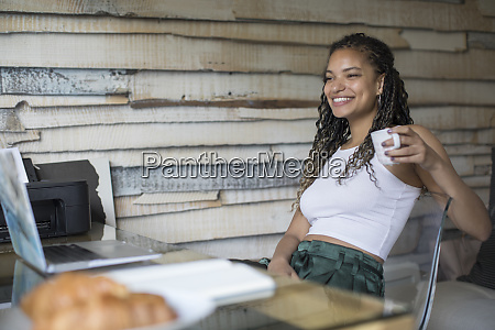 happy young woman drinking coffee at