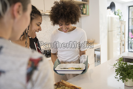 happy young women friends cooking in