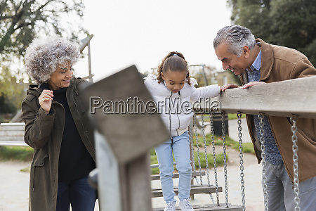 grandparents and granddaughter playing at playground