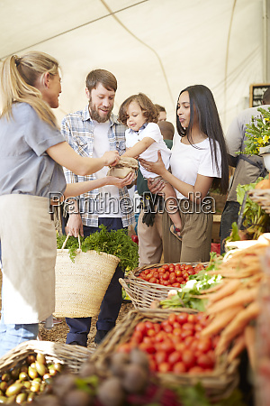 young family shopping at farmers market