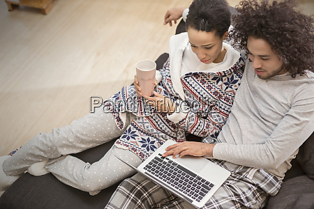 affectionate couple in pajamas relaxing using