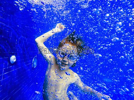 portrait playful boy swimming underwater in
