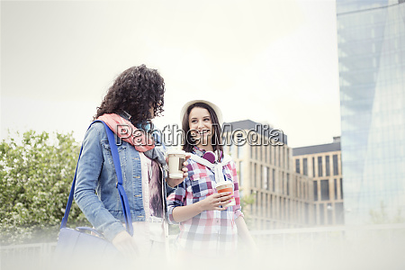 young women friends with coffee walking