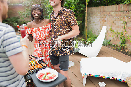 happy young multiethnic couple barbecuing on