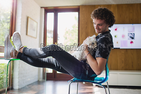 young man petting dog in home