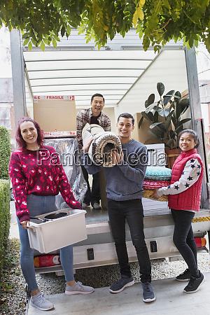 portrait happy friends unloading belongings from