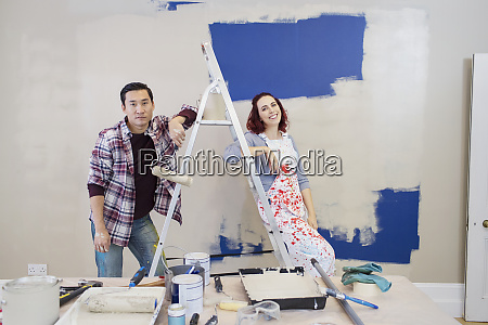 portrait couple redecorating painting wall