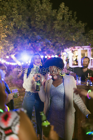 happy friends dancing and drinking at