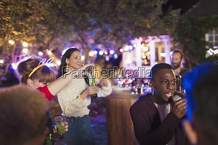 friends drinking and singing karaoke at