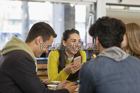 happy young adult friends in cafe