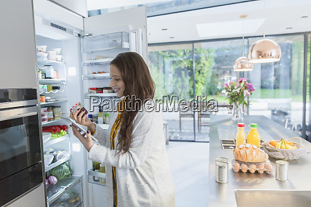 woman with digital tablet at refrigerator