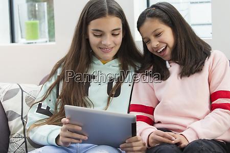 smiling sisters using digital tablet