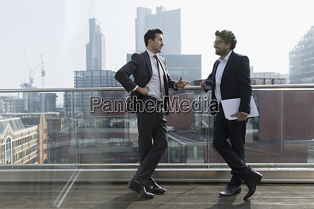 businessmen talking on sunny urban balcony