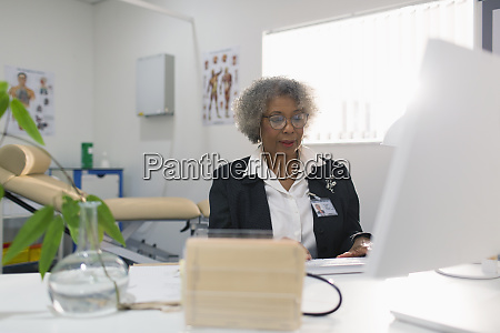 female senior doctor working at computer