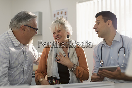 doctor meeting with happy senior couple