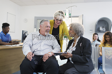 doctor with digital tablet talking to