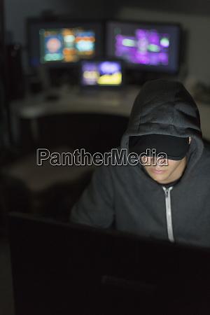 hacker in hoody at computer in